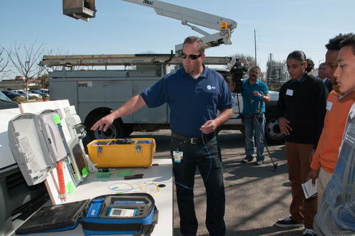An AT&T technician shares a look at equipment with students involved in HACEMOS' annual High Tech Day. ...