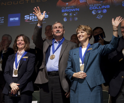 Space shuttle astronauts Bonnie Dunbar (at left), Curt Brown and Eileen Collins acknowledge applause after their induction into the U.S. Astronaut Hall of Fame Saturday at Kennedy Space Center Visitor Complex. They joined an elite group of American space heroes such as Neil Armstrong, Alan Shepard, Jim Lovell and Sally Ride. Brown served as a shuttle pilot three times and commander three times. Collins was the first woman pilot and commander of a shuttle. Dunbar was a mission specialist and payload commander on five shuttle missions. It was the first time two women astronauts have been enshrined together.  (PRNewsFoto/Kennedy Space Center Visitor Complex)