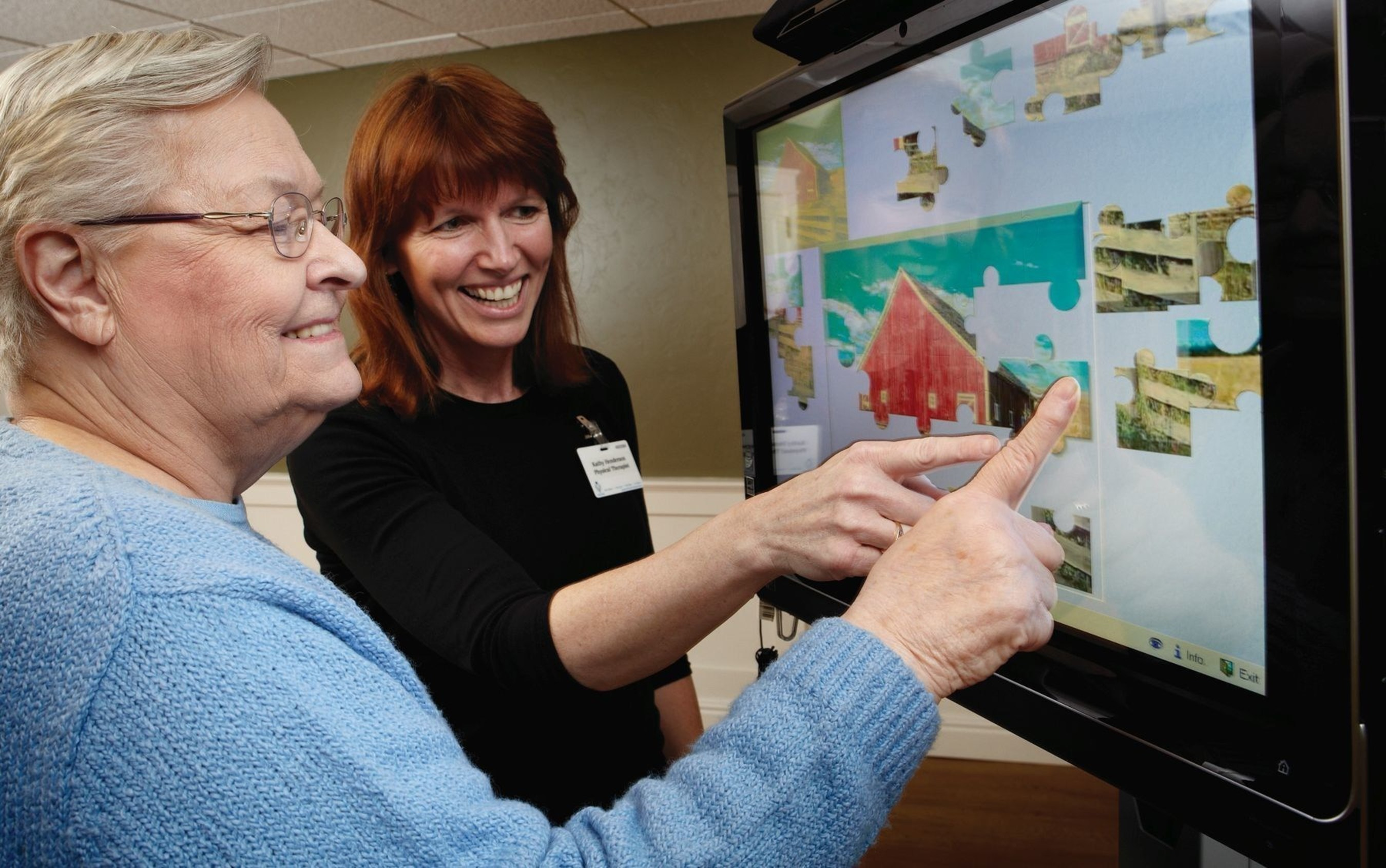 A caregiver uses iN2L technology to foster interaction with a resident. Research shows this technology can revive engagement and strengthen connections with family members.