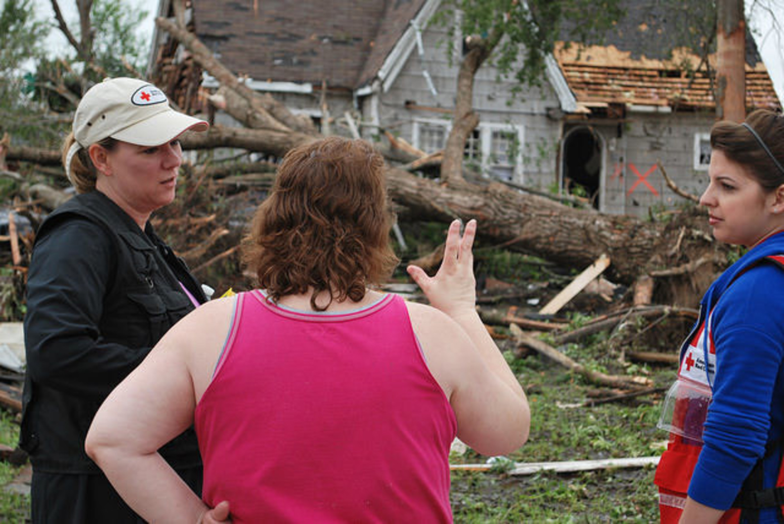 Red Cross workers comfort woman in Van, Texas after a tornado ripped through her home.