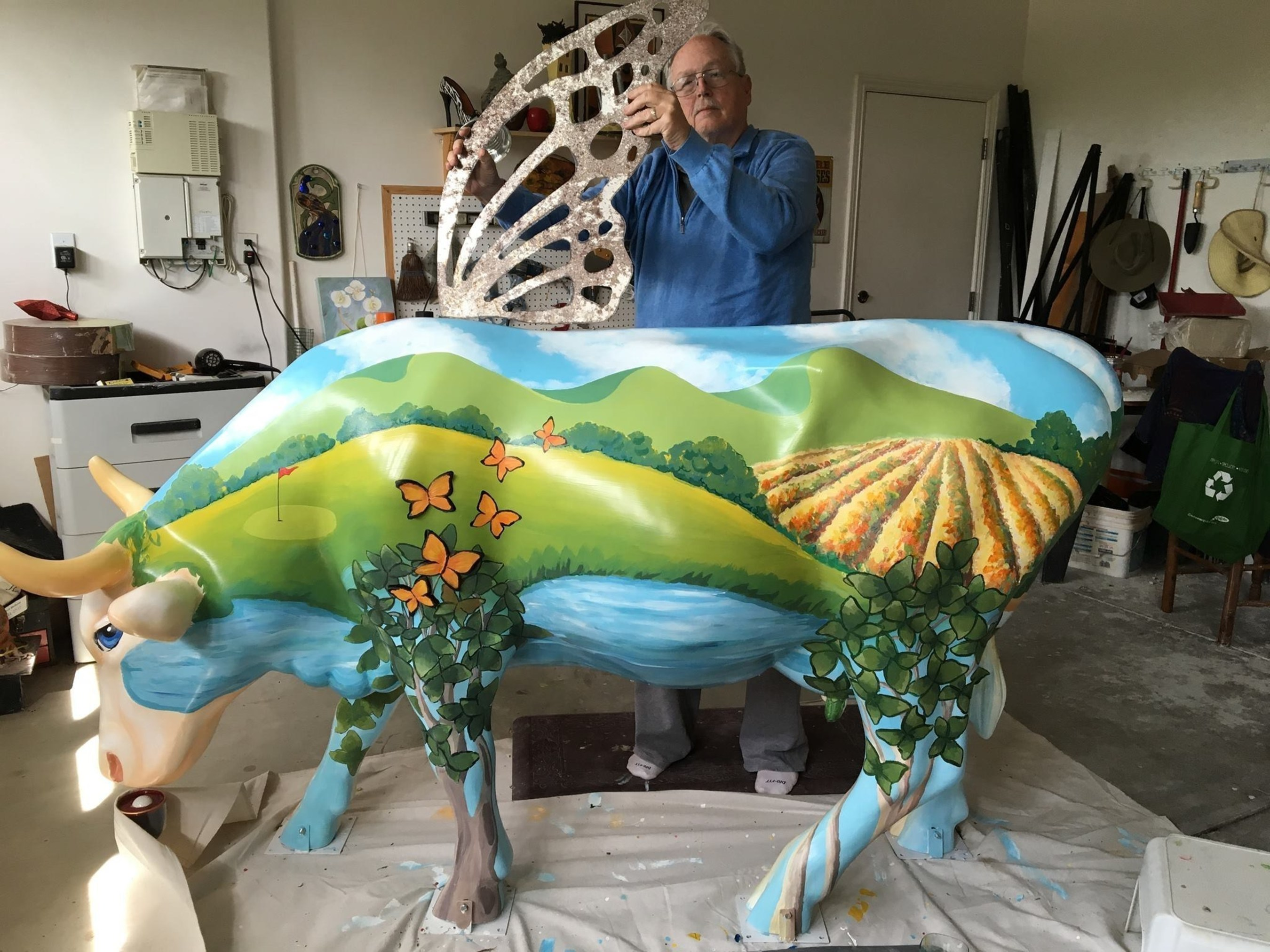 """101 artfully decorated, life-size cows will be on parade during CowParade 2016, taking place this year in San Luis Obispo County on California's gorgeous Central Coast. Pictured: Nipomo, CA artist Karen Floyd's """"NipoMOO,"""" getting finishing touches, including monarch butterfly wings. """"NipoMOO"""" will be just one of 101 cows displayed throughout San Luis Obispo County for CowParade 2016."""