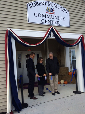 Tom Pollock, Matt Haydinger, and Anita Moore cut the ribbon on the solar electric system at United Communities, Joint Base McGuire-Dix-Lakehurst while dedicating the community center Robert M. Moore.  (PRNewsFoto/Trinity Solar)