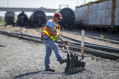 A Union Pacific employee lines a switch to determine the rail car's destination.