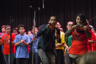 Sir the Baptist performing with students at John Spry Community School as part of Toyota Giving and VH1 Save the Music's grant presentation
