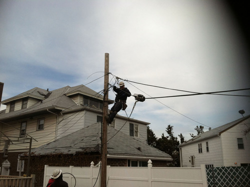 Verizon technicians from Virginia place fiber-optic cable in Seagate, N.J., to restore services after Hurricane  ...