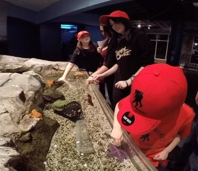 Wounded veterans and their families touch starfish during aquarium visit.