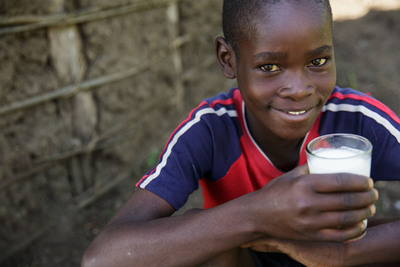A young boy in Kenya enjoying a glass of milk