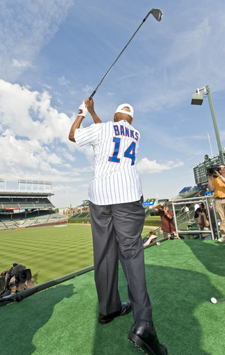 """""""Mr. Cub"""" Ernie Banks tees off from a specially-constructed platform in the stands at Wrigley Field ..."""