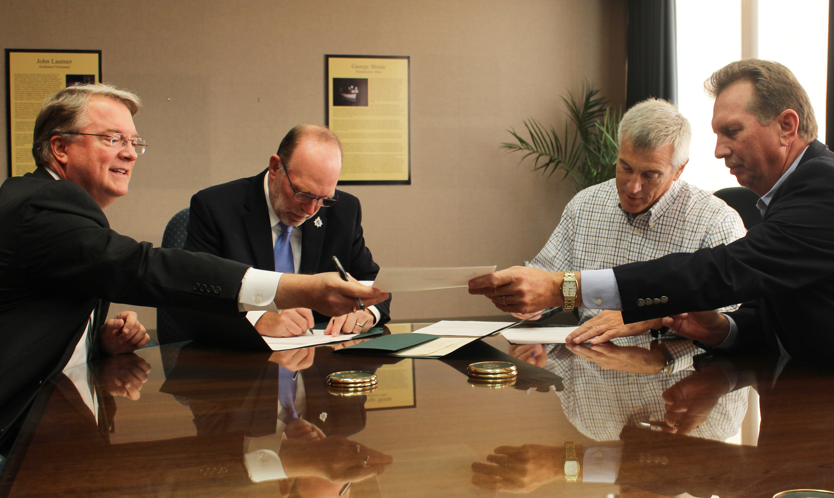 From left: Mark Grambergs, EdR Vice President of Real Estate Development, Northern Michigan University President Fritz Erickson, Neumann Smith's Gene Carroll and Walbridge's Kirk Frownfelter sign a cooperative learning agreement that will offer NMU students the opportunity to get hands-on experience connected to the on-campus housing project currently under construction.