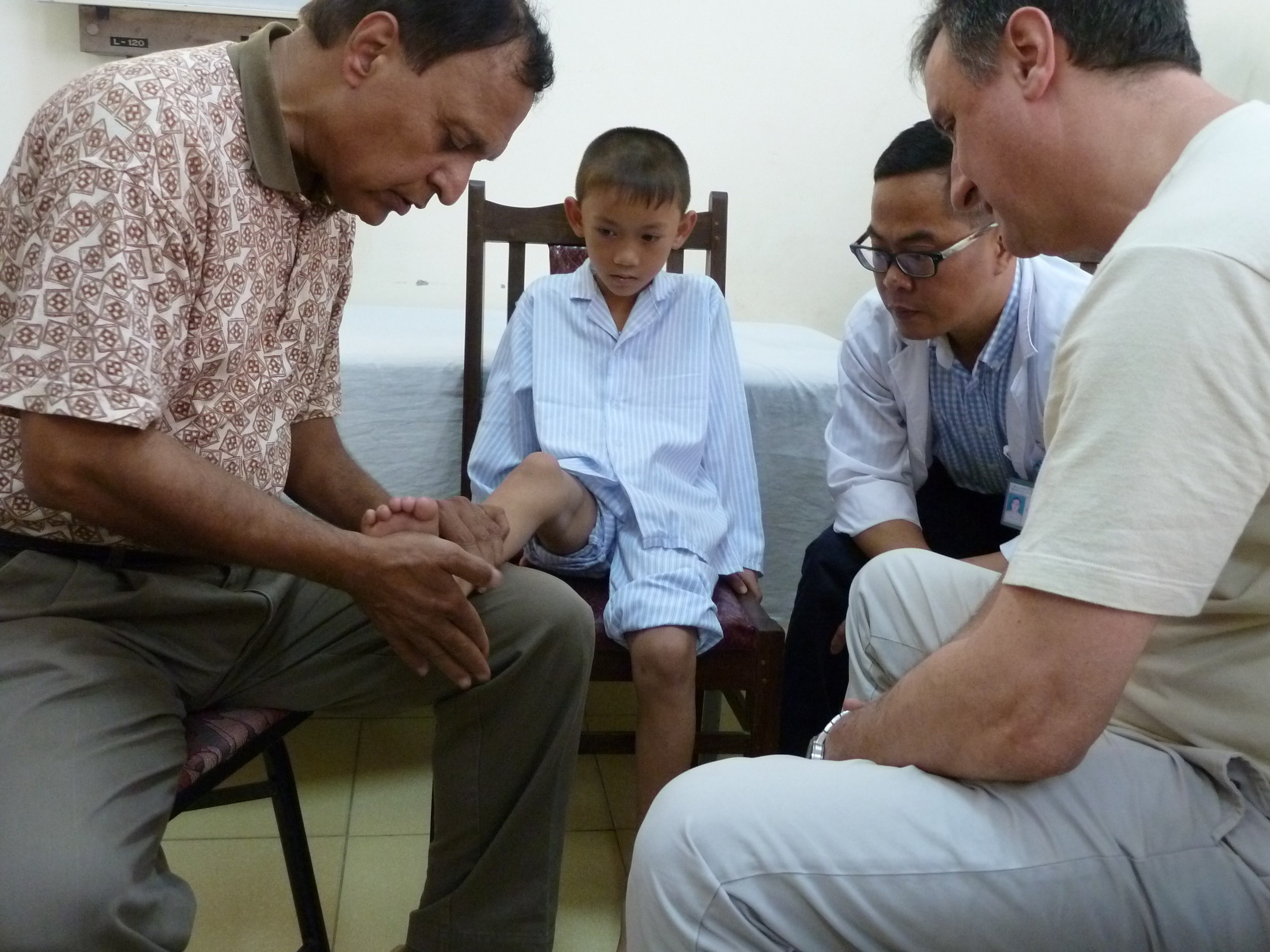 AOFAS volunteers Naren Gurbani, MD (l.) and Mario Adames, MD (r.) evaluate a Vietnamese patient.