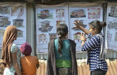 A volunteer for ACT Alliance member DanChurchAid explains to neighbours their options for constructing houses to replace the homes they lost in the 2015 Nepal earthquake. Photo Credit: ACT/Paul Jeffrey (PRNewsFoto/ACT Alliance)