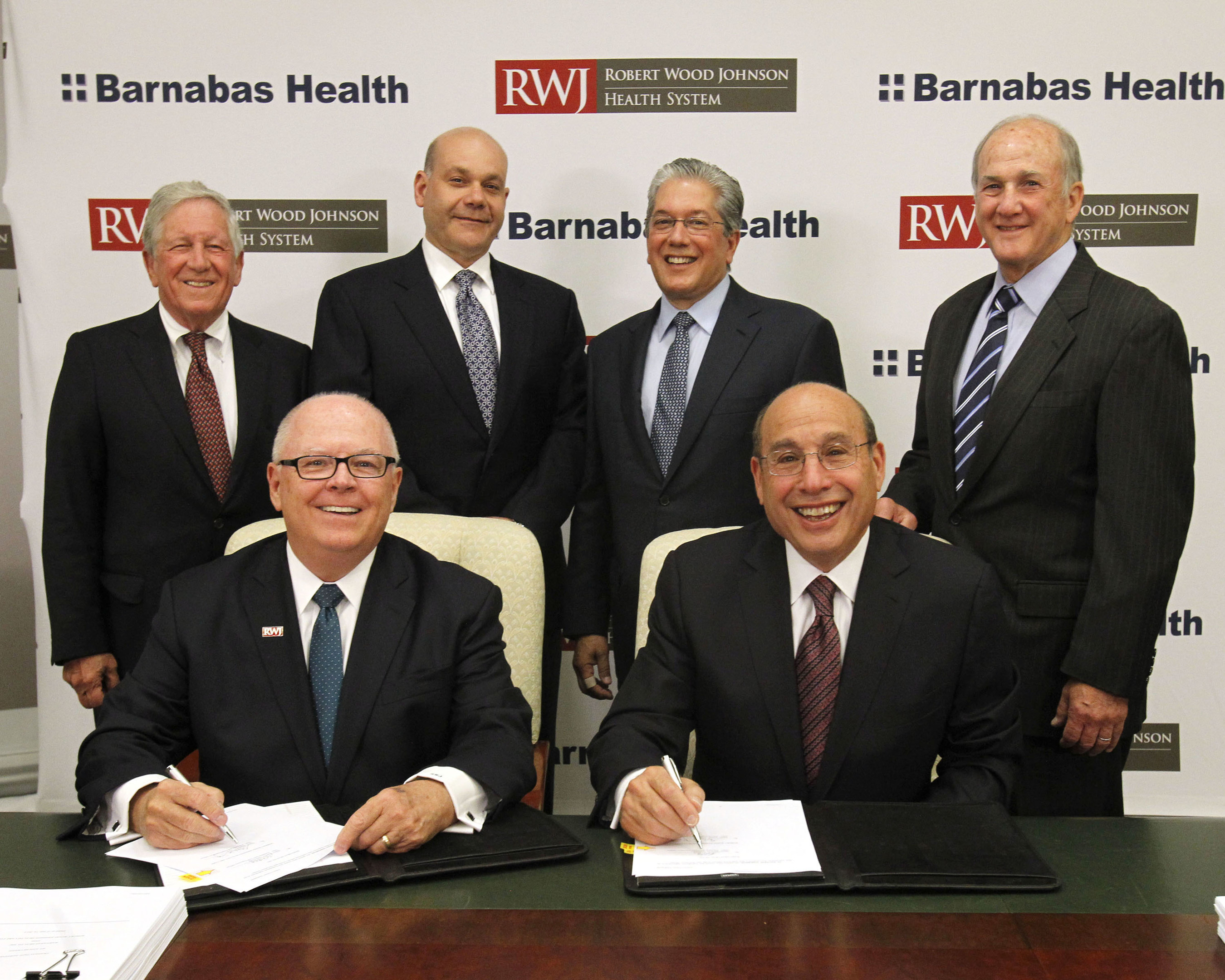 (seated left to right) Stephen K. Jones, President and Chief Executive Officer of Robert Wood Johnson University Hospital and Robert Wood Johnson Health System, and Barry H. Ostrowsky, President and Chief Executive Officer of Barnabas Health, sign the definitive merger agreement. Present for the signing are (left to right) John Hoffman, Esq., Chair of Robert Wood Johnson Health Care Corp. Board; Jack Morris, Chair of the Robert Wood Johnson University Hospital Board; Marc E. Berson, Chair, Barnabas...