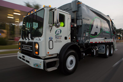 Advanced Disposal residential rear load vehicle in motion on municipal street.
