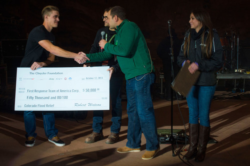 During the Jeep(R) Celebration Concert featuring the Counting Crows at Red Rocks Amphitheatre, Jeff Hines, Chrysler Group director of the Denver business center (right), presents Tim Wolkowicz (far left) and Tad Agoglia (left) of the First Response Team of America, with a check for $50,000 from The Chrysler Foundation. The donation will enable the disaster-relief organization to continue its flood recovery efforts in Colorado.  (PRNewsFoto/Chrysler Group LLC)