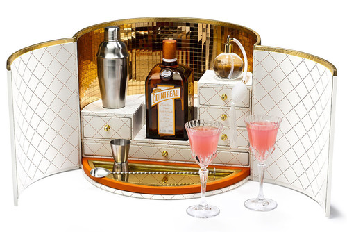 "Together with Cointreau, the original French triple sec, Dita Von Teese launches ""My Cointreau Travel Essentials"" in the United States. Presented in a chic, retro hatbox, the luxury coffret opens up to reveal a beautiful travel bar that conveniently contains all the accessories needed to create original cocktails while jet setting around the globe or while celebrating at home with friends. The white and grained-leather finished mini bar is equipped with a jigger for measuring; a special bar spoon; two vintage-inspired glasses; a silver  ..."