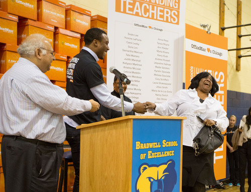 Chicago Cook Elementary School teacher Yvonne LeFlorie greets pro football player Brandon Marshall, middle, and OfficeMax CEO Ravi Saligram after winning $1,000 worth of classroom supplies at OfficeMax's A Day Made Better teacher event at Bradwell Elementary School in Chicago Thursday January 31, 2013.  OfficeMax joined CPS CEO Barbara Byrd-Bennett and Marshall in surprising 100 Chicago Public Schools teachers at the event with $100,000 total in school supplies.  Since 2007, A Day Made Better and other OfficeMax Goodworks programs have ...
