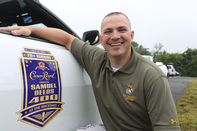 """Retired Gunnery Sergeant Samuel Deeds poses next to an Indianapolis Motor Speedway (IMS) pace car bearing the official logo for the Summer Sprint Cup Series Race at IMS during an event in Erlanger, Ky. on Thursday, June 27, 2013. As winner of Crown Royal's """"Your Hero's Name Here"""" program, Deeds will receive naming rights to that race, taking place on July 28, 2013.  (PRNewsFoto/Diageo)"""