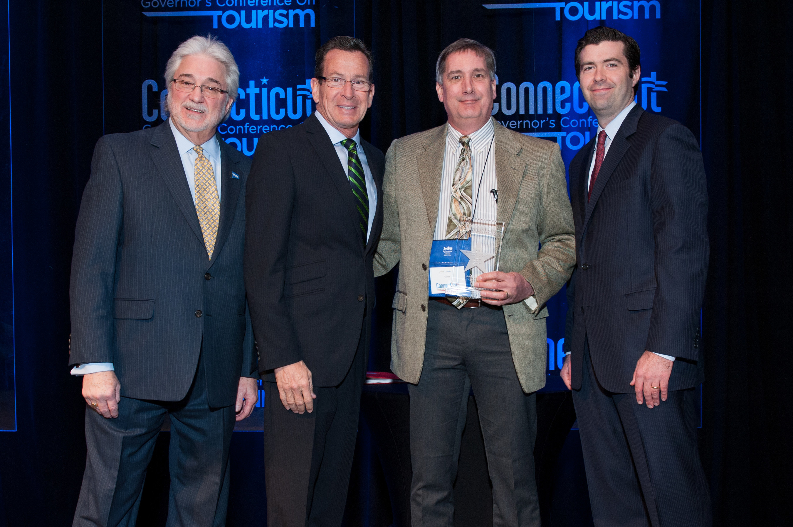 John Lyman III, Executive Vice President of Lyman Orchards (Middlefield) receives the 2016 Connecticut Governor's Tourism Award for Tourism Legacy Leader. From left: Randy Fiveash, Director, Connecticut Office of Tourism; Governor Dannel P. Malloy; John Lyman III, Executive Vice President, Lyman Orchards; Tim Sullivan, Deputy Commissioner, Connecticut Department of Economic and Community Development.