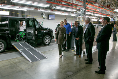 Right to left  - Indiana Sen. Joe Donnelly AM General President and CEO, Andy Hove, AM General, Commercial President, Howard Glaser and Mrs. Clinton paused during their tour of the AM General Commercial Assembly Plant to witness Mobility Ventures employee, and former Ms. Wheelchair America, Erika Bogan demonstrate the innovative MV-1 vehicle that redefines accessible transportation for people with disabilities.