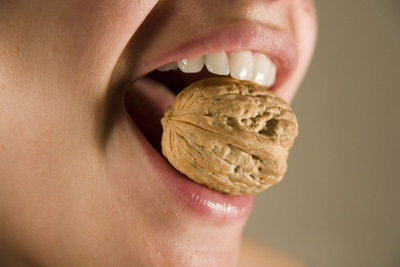 Millions of American can crack a walnut with their teeth. While most adults exert about 20 to 40 pounds of pressure when their teeth make contact, millions of Americans exert as much as 250 pounds of pressure on their teeth -- enough to crack a walnut. These teeth grinders are known as bruxers.  (PRNewsFoto/Manhattan Dental Arts)