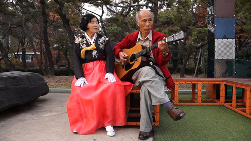 A scene from the movie. An old lady is singing a song in accordance with guitar playing.  (PRNewsFoto/Seoul ...