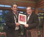Peregrine's CEO Jim Cable (left) presents Yoshitaka Fujita Murata's Executive Deputy President and Member of the Board of Directors with a commemorative plaque congratulating Peregrine's pending parent company on 70 years of electronics innovation.