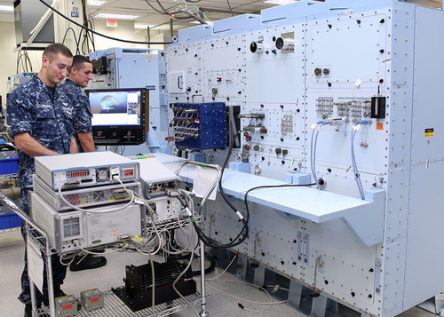 Petty Officers Third Class Ira Schwartz (left) and Devin Riley, both aviation electronics technicians, perform ...