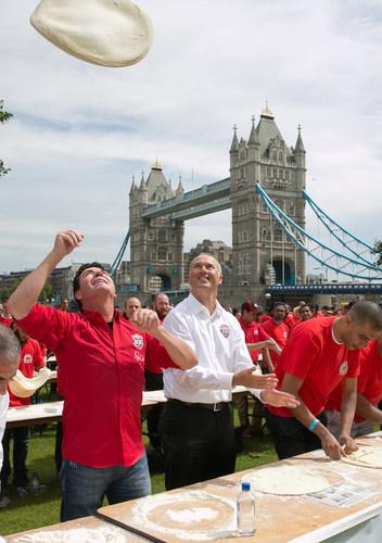 John Schnatter, Founder of Papa John's, demonstrates how a skilled pizza maker tosses dough. (PRNewsFoto/Papa John's) (PRNewsFoto/Papa John's)