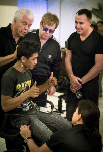 Sir Elton John, David Furnish and Starkey Hearing Foundation founders Bill and Tani Austin help a young man hear during the Foundation's mission in Manila, Philippines on December 8.  (PRNewsFoto/Starkey Hearing Foundation)