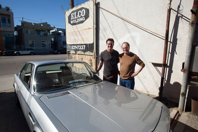 Race car enthusiast and inventor Mike Pethel (left) stands with BURN Host Alex Chadwick outside Elco Welding in Venice, California, with his super fast, battery-powered green car.  The 1970s-era BMS 3.0 CS is powered by two electric motors and five lithium ion phosphate batteries capable of generating 800 horsepower in the blink of an eye.  The experimental car can go zero to 60 mph in roughly three seconds.  (PRNewsFoto/The Busby Group)