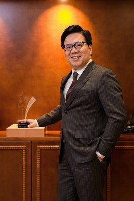 Sands China Ltd. President Dr. Wilfred Wong stands next to the company's Outstanding Contribution Award trophy from the Summit Forum for the Development of Foreign Enterprises in China.
