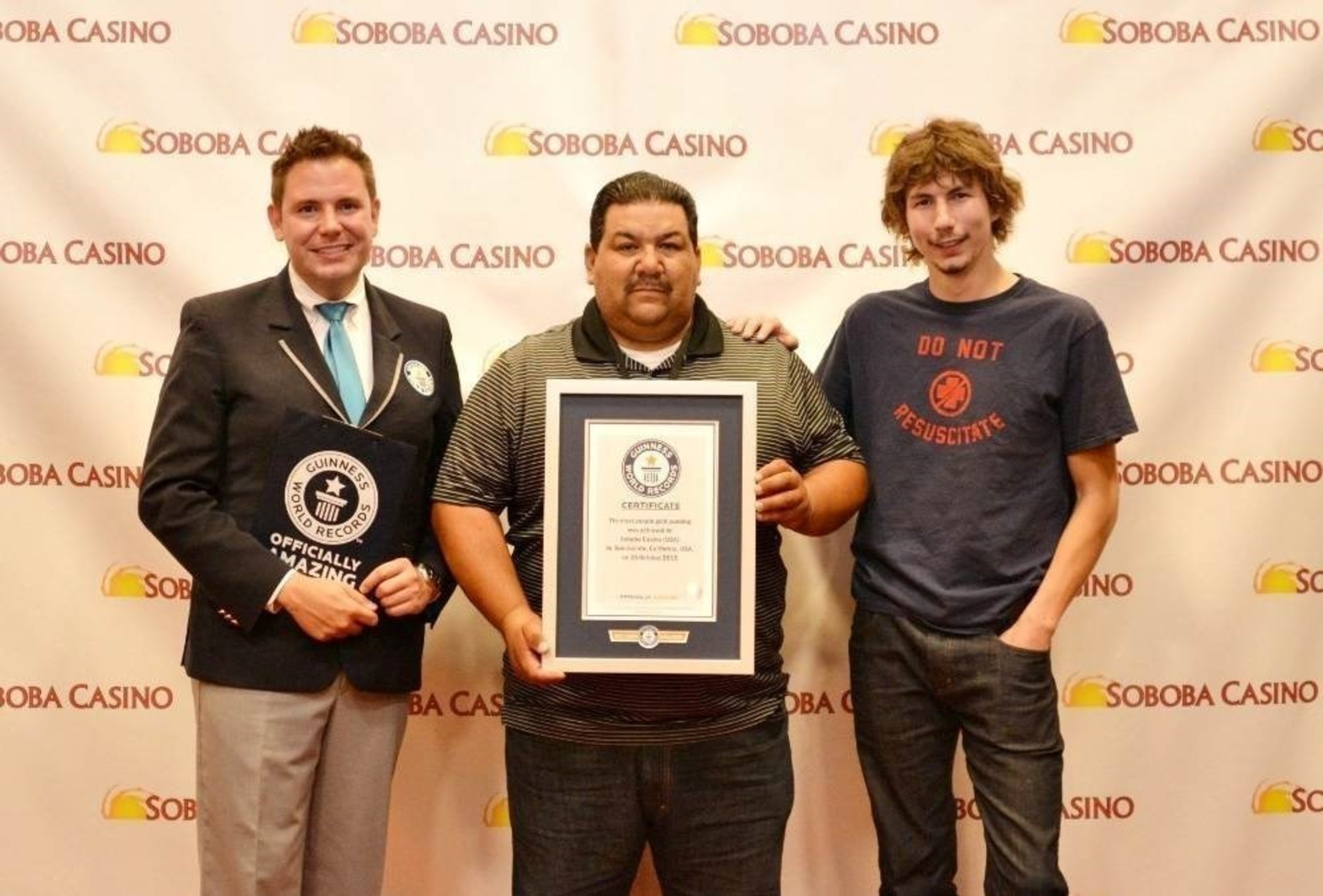 """Guinness Book of world Records Michael Empric, Vice-Chair of Soboba Band of Luiseno Indians Tribal Council Isaiah Vivanco, and Star of Discovery Channel's Gold Rush Parker Schnable celebrate breaking a """"Golden"""" World Record."""
