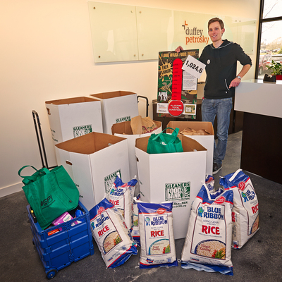 Jim VanHavermaat of Duffey Petrosky stands with Gleaners Food Bank donation raised by Duffey Petrosky and Embark Digital employees.