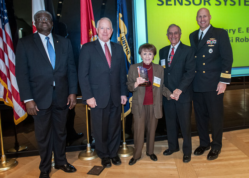 Betty Robin and Si Robin (second from right), the husband and wife leadership team of Los Angeles-based Sensor Systems, Inc., receive a Recognition for Excellence Gold Award as one of the government's best suppliers from the DLA Land and Maritime Commander, Navy Rear Adm. David R. Pimpo (far right). Also shown are (far left) Land and Maritime Acquisition Director Milton K. Lewis and Deputy Commander James M. McClaugherty. Sensor Systems supplies communication and navigation antennas for aircraft for the Department of Defense and other ...