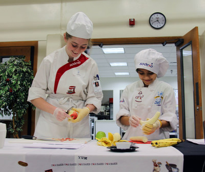 A sodexo chef lends a hand and some culinary guidance to a student at a Sodexo Future Chefs event.