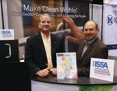 NanoSeptic co-founders, Hackemeyer and Sisson, in front of their exhibit displaying sample facility touch points, innovation award plaque, and the cover story for ISSA Magazine - The Psychology of Clean, authored by Sisson