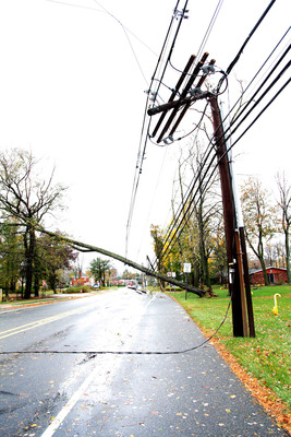 A large tree uprooted by Hurricane Sandy hangs across a Morristown, NJ road supported only by power and other utility lines.  The tree will be removed and the utility poles on either side of the tree will be replaced before power can be restored.  (PRNewsFoto/FirstEnergy Corp.)