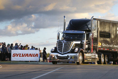 "A NASCAR(R) hauler driver makes his way into the infield for the SYLVANIA 300 race weekend at New Hampshire Motor Speedway during the sixth annual Hauler Parade on Sept. 24, 2015. The Hauler Parade is the kick-off to race weekend and brings SYLVANIA Automotive Lighting's ""Hauler Headlights for Safer Nights"" initiative full circle as many big rigs pull in with new SYLVANIA headlight bulbs in to guide their way."