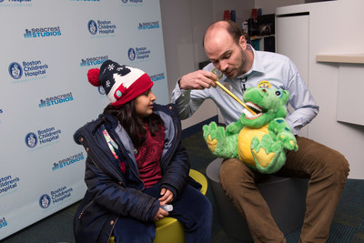 Dr. Brian Novy, Director of Practice Improvement, DentaQuest Institute, demonstrates proper tooth-brushing technique with a young attendee at a recent dental fair at Boston Children's Hospital celebrating the endowment and partnership.