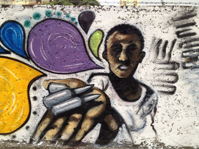 Amnesty International activists painted the streets of Caracas, Venezuela with the message 'Stop the Bullets', during a week of action against Gun Violence. Emmanuel Jal was a child soldier like the boy depicted in this mural.  (PRNewsFoto/Amnesty International)