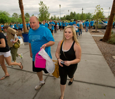 "Lauren Regnier, 18, of Gilbert, walks with volunteer Marshal Moore, a Grand Canyon University admissions staff member. GCU faculty and staff volunteers helped move new students into the residence halls on Thursday as part of the annual ""Luggage Lugger"" move-in event.  (PRNewsFoto/Grand Canyon University)"