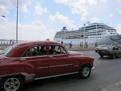 A classic American car serving as a taxi in Havana drives past Carnival Corporation's Fathom Adonia cruise ship -- which on May 2 became the first U.S. cruise ship in over 50 years to sail from the U.S. to Cuba.