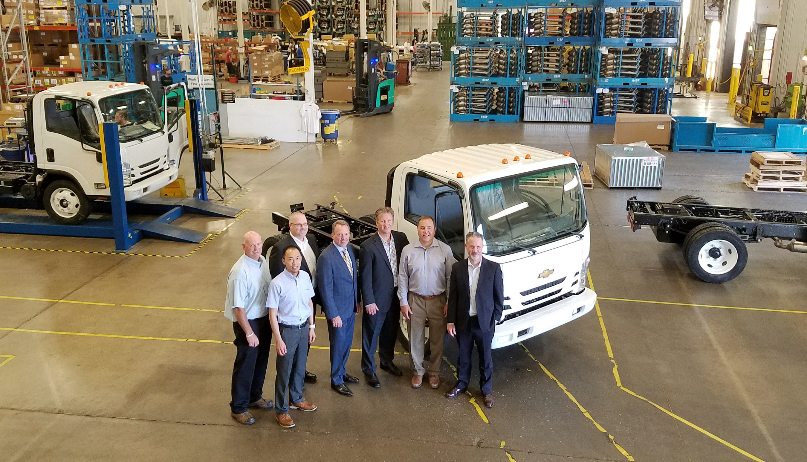 First Chevrolet Medium Duty Truck Rolls Off the Line at Spartan Motors. People- Left from right: Thomas A. Meisel, Isuzu North America Corporation, Takusei Nakagawa, VP CV Product Planning, Isuzu North America Corporation, Kevin Brewer, Medium Duty Marketing and Sales Manager, General Motors Fleet, Daryl Adams: President and CEO, Spartan Motors, John Schwegman, U.S. Director of Commercial Product, General Motors Fleet, Steve Guillaume, President, Spartan Specialty Vehicles, Paul Loewer, Medium Duty Product Manager, General Motors Fleet