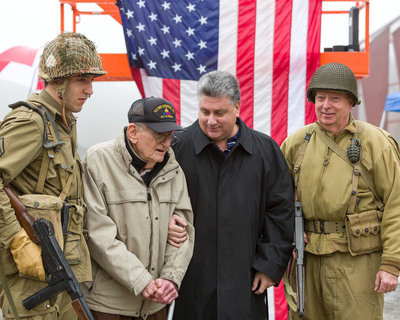 Steve Napolitano, President and CEO of First Nationwide Title Agency, greets WW II veteran Irving Greger who fought during the Battle of the Bulge in December of 1944 when he and thousands of Americans withstood a murderous assault by German ground and armor forces. The two are joined by living historians during tribute ceremonies at the Museum of American Armor in Nassau County, Long Island. Mr. Napolitano's father was a soldier in General George Patton's army during that conflict.  (PRNewsFoto/First Nationwide Title Agency)