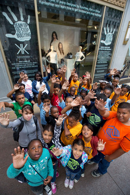 Children from the Boys and Girls Club of Chicago raise their hands to show their commitment to Team Up to Stop Bullying at the Sears State Street store on Monday, August 5, 2013 in Chicago. Sears revealed a window display, featuring jeans designed by Kim, Khloe and Kourtney Kardashian to raise awareness about bullying solutions as students head back to school. The decorated jeans - featuring the autograph and handprint of each celebrity sister to symbolize her commitment to end bullying - will be awarded to winners of a Shop Your Way Rewards sweepstakes, with Sears making a donation to the non-profit charities associated with Team Up to Stop Bullying for every entry. (John Konstantaras / AP Images for Sears).