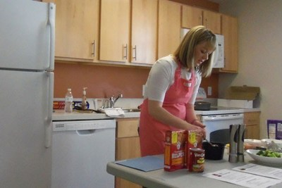 Nicola Lodes, a Raytheon Intelligence, Information and Services employee, led a cooking class at Victory Apartments in Omaha, Nebraska. The apartment complex aims to help homeless veterans regain the ability to support themselves.