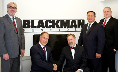 (Center R-L) David Krakoff and Robert Mannheimer seal the companies' new distribution deal with a handshake. They are flanked (L-R) by David Lyon, Director of Showrooms, Blackman Plumbing Supply; Jason Fitzsimmons, Vice President, United States Sales Division, TOTO USA; and Kevin Burns, Regional Director, Northeast Region, United States Sales Division, TOTO USA.