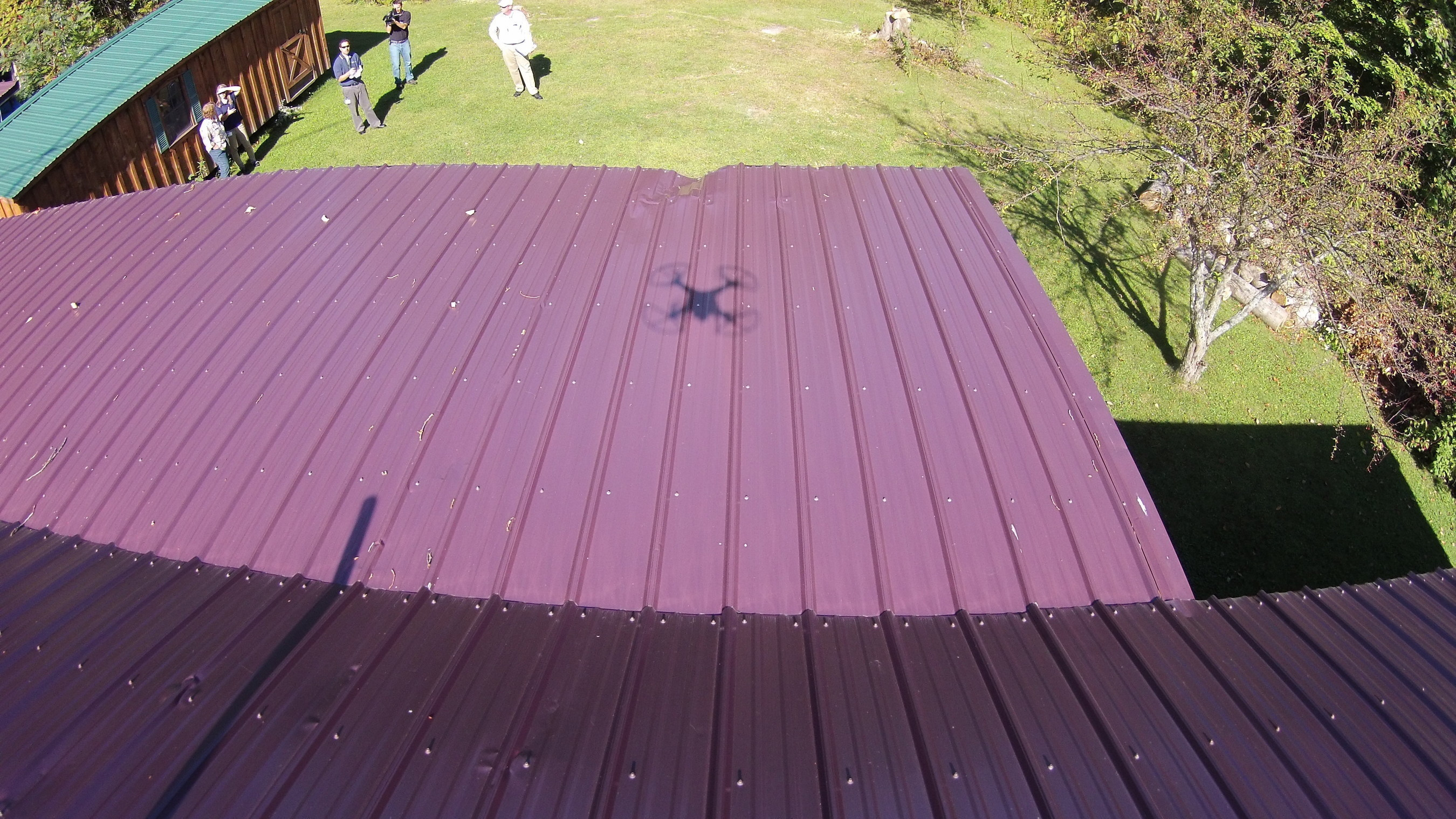The shadow of a drone can be seen hovering over a roof in Waterford, Penn., while representatives of Erie Insurance look on. In what could be the first step toward changing how insurance claims are handled in the future, Erie Insurance has moved from testing to actually using a drone to assist with a property damage claim. It is not aware of any other insurance company that has used a drone in an actual claim. The drone was used to inspect a roof after it had been repaired.