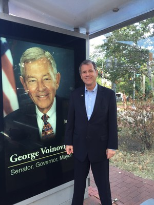 Sen. Sherrod Brown (D-Ohio) poses in front of one of the many digital signs that have dotted Washington D.C. bus shelters today commemorating the life of the late Senator George Voinovich.