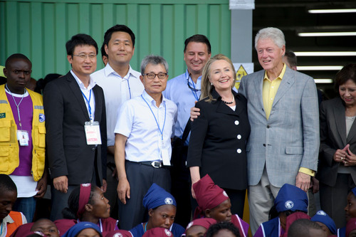 Group Photo with Sae-A CEO Tae-Hyung Kim, Sae-A Chairman Woong-Ki Kim, US Secretary of State Hillary Clinton, Former President Bill Clinton and Sae-A Factory Employees for the Opening Ceremony.  (PRNewsFoto/Sae-A Trading Co., Ltd.)